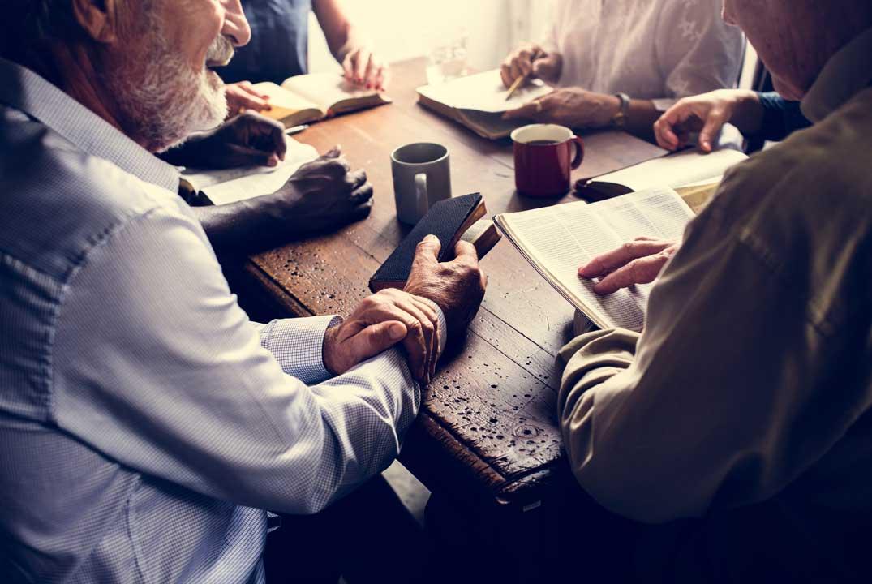 groupe échangeant autour d'un café, bibles en mains