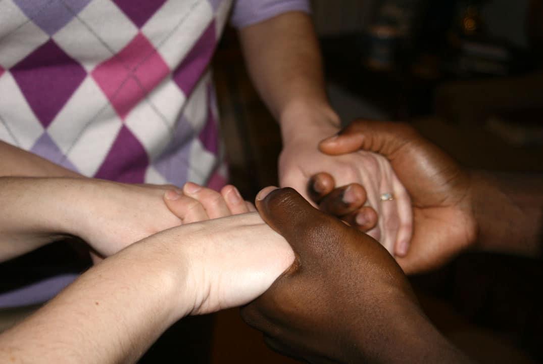 femmes se tenant les mains dans la prière