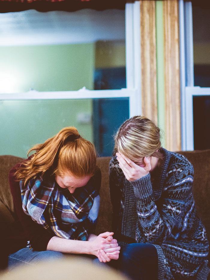 deux femmes sur un canapé en prière